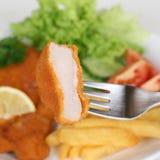 Äta schnitzelkotlettkotletten med gaffeln Arkivfoto