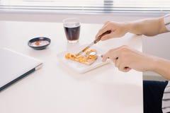 Äta smaklig pizza på arbetetabellen på kontoret arkivfoto