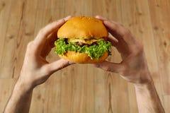 Äta snabbmat Räcker den hållande hamburgaren Punkt av sikten Nutrit Royaltyfri Bild