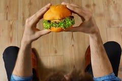 Äta snabbmat Räcker den hållande hamburgaren Punkt av sikten Nutrit Arkivbild