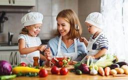 äta som är sunt Den lyckliga familjmodern och barn förbereder veg royaltyfri fotografi