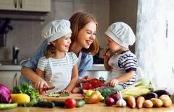 äta som är sunt Den lyckliga familjmodern och barn förbereder veget fotografering för bildbyråer