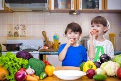 äta som är sunt Lyckliga barn förbereder och äter grönsaksallad royaltyfria foton