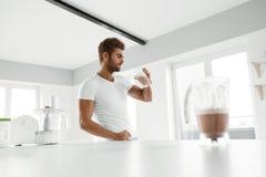 äta som är sunt Muskulös man som inomhus dricker sportskakadrinken arkivbilder