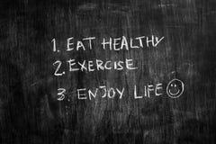 Äta sunt och övningen som är skriftliga på svart tavla Royaltyfria Bilder