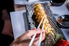 Äta sushi med pinnar Arkivfoto