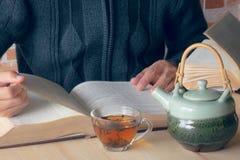 Äta te på läsning royaltyfria bilder