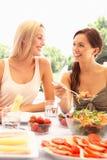 äta utomhus unga kvinnor Royaltyfri Bild