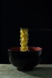 Äta varma nudlar, den svarta bakgrunden, läcker svart för ögonblickliga nudlar Arkivfoto