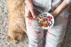 Äta yoghurt med granola och bär Kvinnligt sund frukost för äta arkivbild