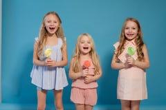 Äten söt godisklubba för tre små flickor flickvän på en pinne royaltyfri fotografi