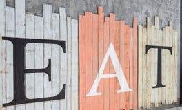 """"""" ÄTER """"attraktion på träbakgrundstappningstil Royaltyfri Bild"""