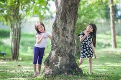 Äter avslappnande lek för två små flickor i parkera och klubbor royaltyfri fotografi