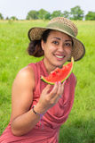 Äter den bärande hatten för kvinnan den nya melon utanför Arkivbilder