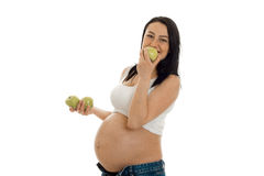 Äter den gravida flickan för barn gröna äpplen som isoleras på vit bakgrund Fotografering för Bildbyråer