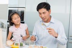 Äter den hållande ögonen på fadern för lilla flickan mat med en gaffel i kök Arkivfoton