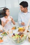 Äter den hållande ögonen på lilla flickan för fadern mat i kök Arkivfoto