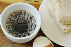 Äter den hela vetesmörgåsen för tonfisk på plattan och det kokta ägget par med koppen för svart kaffe Royaltyfri Foto