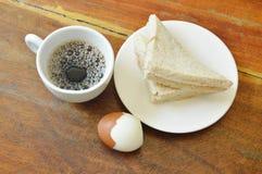 Äter den hela vetesmörgåsen för tonfisk på plattan och det kokta ägget par med koppen för svart kaffe Arkivbilder