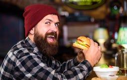 Äter den hungriga mannen för hipsteren hamburgaren Mannen med skägget äter hamburgaremenyn Sitter den skäggiga mannen för den bru arkivbild