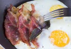 Äter den hurtiga frukosten stekt ägg och bacon i en stekpanna med Royaltyfri Fotografi