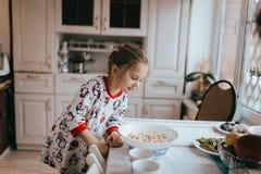 Äter den iklädda pajamaen för den trevliga lilla flickan popcorn i kök arkivfoton