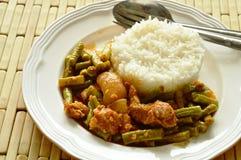 Äter den kryddig uppståndelse stekt lång bönan för gården och fettgrisköttcurry par med ris Arkivbild