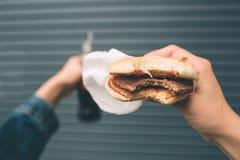 Äter den lyckliga flickan för den lilla frukosten snabbmat- och drinkcola över nära den gråa väggen Royaltyfri Foto