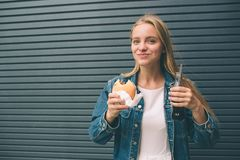 Äter den lyckliga flickan för den lilla frukosten snabbmat- och drinkcola över nära den gråa väggen arkivfoton