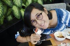 Äter den söta efterrätten för den thailändska kvinnashowen för i restaurang av hotellet Fotografering för Bildbyråer