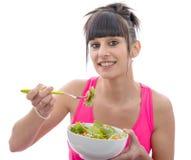 Äter den sportiga kvinnan för den unga brunetten sallad Royaltyfri Fotografi