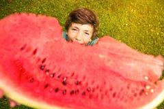 Äter den stiliga pojken för preteenen vattenmelon Arkivbild