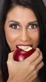 Äter den stor brunt synade kvinnan röd matfrukt - läckra Apple Royaltyfri Foto