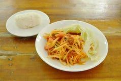 Äter den thailändska kryddiga gröna papayaen för Somtumen med inlagd musslasallad klibbiga ris för par på plattan Royaltyfri Foto