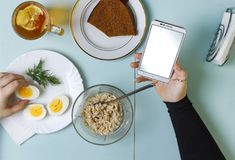 Äter den unga affärskvinnan för den sunda frukosten eller barnstudenten frukosten på tabellen hemma eller på en coffee shop eller Arkivbild
