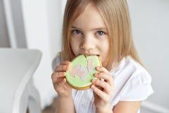 Äter det härliga barnet för närbilden pepparkakaägg Lycklig familj som förbereder sig för påsk royaltyfria foton