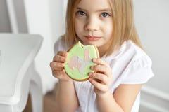 Äter det härliga barnet för närbilden pepparkakaägg Lycklig familj som förbereder sig för påsk fotografering för bildbyråer