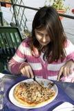 äter flickan little pizza Royaltyfri Bild