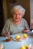 Äter heerful kvinnor för äldre Ñ- sammanträde på matställetabellen hemma Royaltyfria Foton