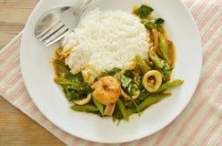 Äter kryddig uppståndelse stekt räka- och tioarmad bläckfiskcurry par med ris Fotografering för Bildbyråer