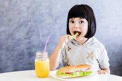 Äter lilla flickan för svart hår för cuttlen som har frukosten och, grönsallat Royaltyfri Fotografi