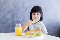 Äter lilla flickan för svart hår för cuttlen som har frukosten och, grönsallat Arkivbild