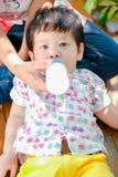 Äter lycklig smilling för gullig liten asiatisk pojke mjölkar i parkerar utomhus, lyckliga ungar arkivbild