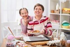 Äter stekheta kakor för modern och för dottern, flicka kakan, den hem- kökinre, sunt matbegrepp Royaltyfri Fotografi