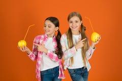 Äter tillfällig stil för flickaungar orange bakgrund för äpplefrukt Skolflickor äter äpplefrukt Skola lunch Vitaminfrukt royaltyfri fotografi