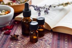 Ätherische Öle mit Kräutern und Buch lizenzfreies stockbild