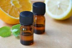 Ätherische Öle mit Zitrusfrüchten und Kräutern Stockbild