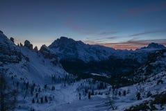 Ätherischer Sonnenuntergang im schneebedeckten Gebirgstal Lizenzfreies Stockbild