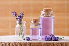 Ätherisches Öl in den Glasflaschen und im frischen Lavendel blüht auf Stumpf und braunem Hintergrund Stockbilder