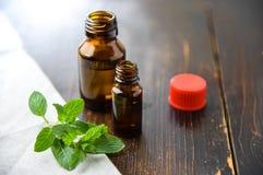 Ätherisches Öl der Pfefferminz in einer kleinen braunen Flasche mit frischer grüner Minze auf einem alten hölzernen Hintergrund,  Lizenzfreie Stockbilder
